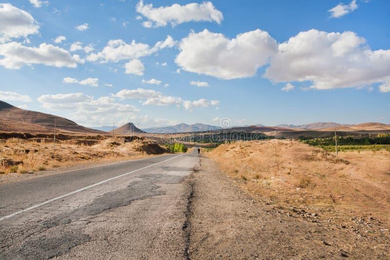 Carretera de asfalto quebrada en el valle de la hierba seca del Oriente Medio debajo de las nubes blancas imágenes de archivo libres de regalías