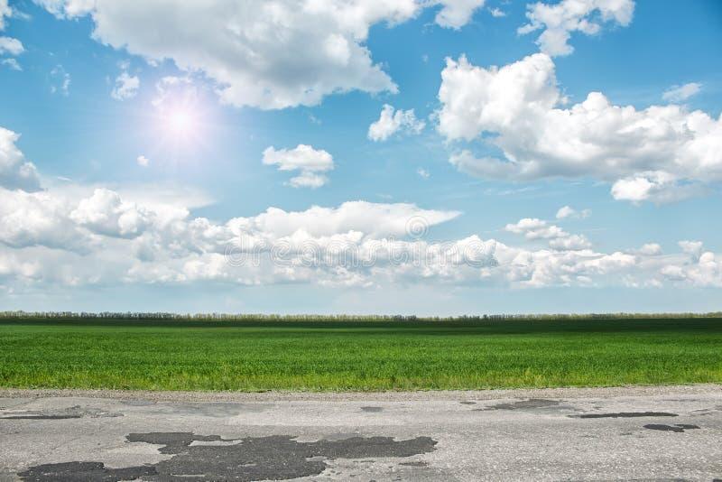 Carretera de asfalto y campo verde en el día de verano soleado imágenes de archivo libres de regalías