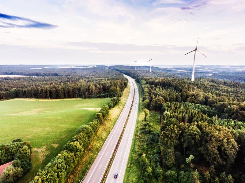 Carretera en el bosque verde, molinoes de viento, cielo nublado netherlands fotos de archivo