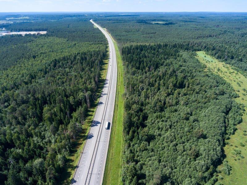 Carretera larga y ancha que va al horizonte, impulsiones en carril, visión aérea del semi-remolque de la carga foto de archivo libre de regalías