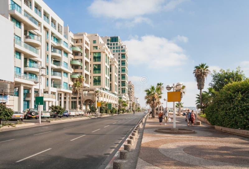 Carretera a lo largo del terraplén con los edificios en el lado, el estacionamiento y la gente del camino caminando adelante imagen de archivo libre de regalías
