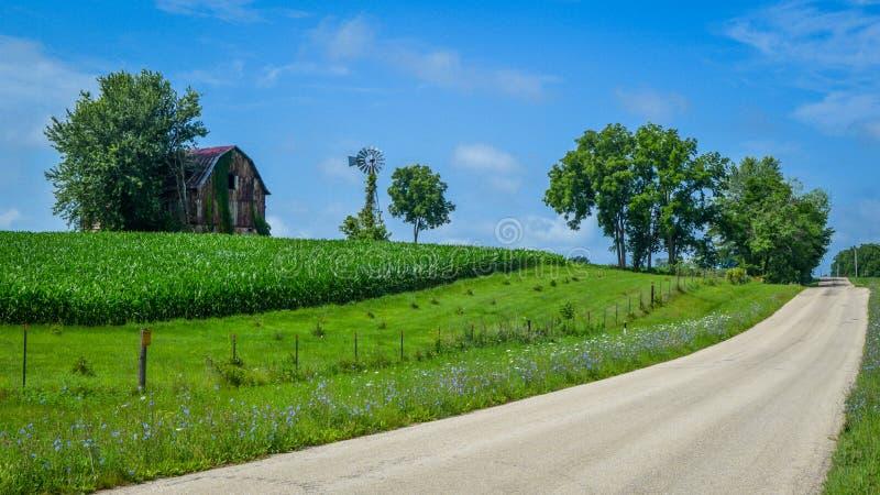 Carretera nacional con el granero, el molino de viento y el maíz fotografía de archivo