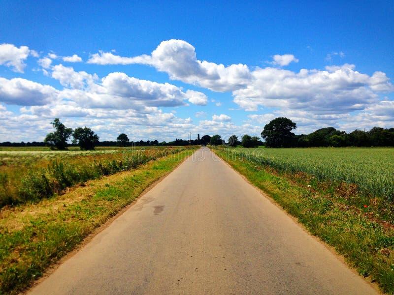 Carretera nacional larga, recta con los campos y cielo azul en Lincolnshire, Inglaterra fotografía de archivo