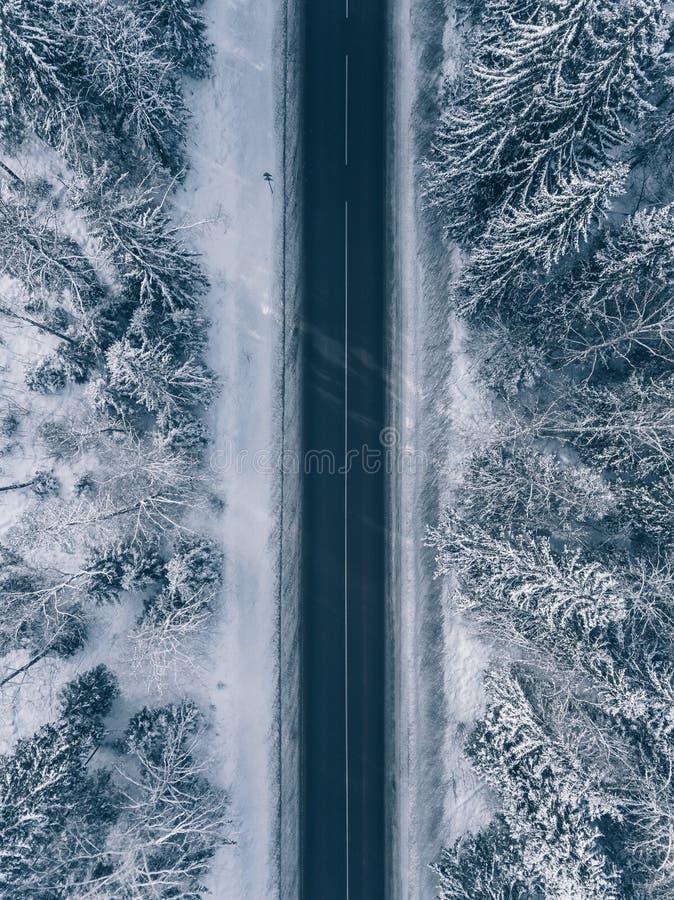 Carretera nacional que pasa con los paisajes nevados hermosos Silueta del hombre de negocios Cowering foto de archivo