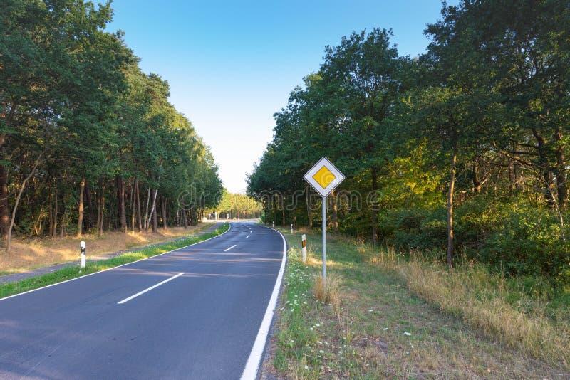 Carretera nacional que serpentea con un área verde del bosque y del pueblo imágenes de archivo libres de regalías