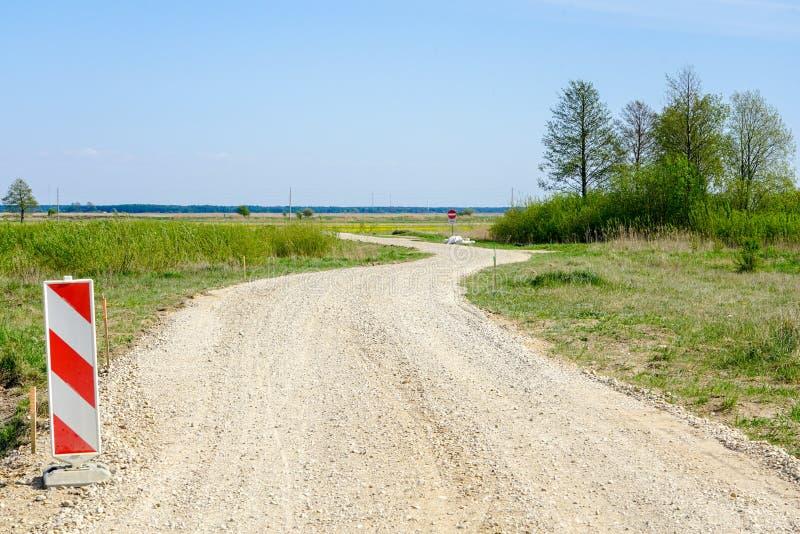 Carretera nacional rural de enrrollamiento, señal de peligro en el primero plano imágenes de archivo libres de regalías