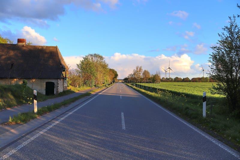 Carretera nacional vac?a sin coches con algunos ?rboles y un cielo azul encontrado en Alemania septentrional fotos de archivo