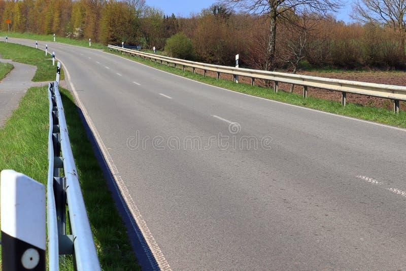 Carretera nacional vac?a sin coches con algunos ?rboles y un cielo azul encontrado en Alemania septentrional imagen de archivo libre de regalías