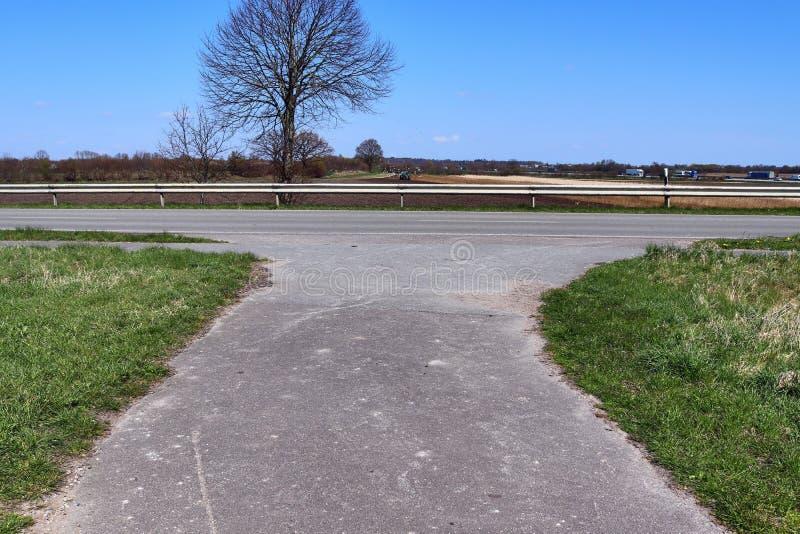 Carretera nacional vac?a sin coches con algunos ?rboles y un cielo azul encontrado en Alemania septentrional fotos de archivo libres de regalías