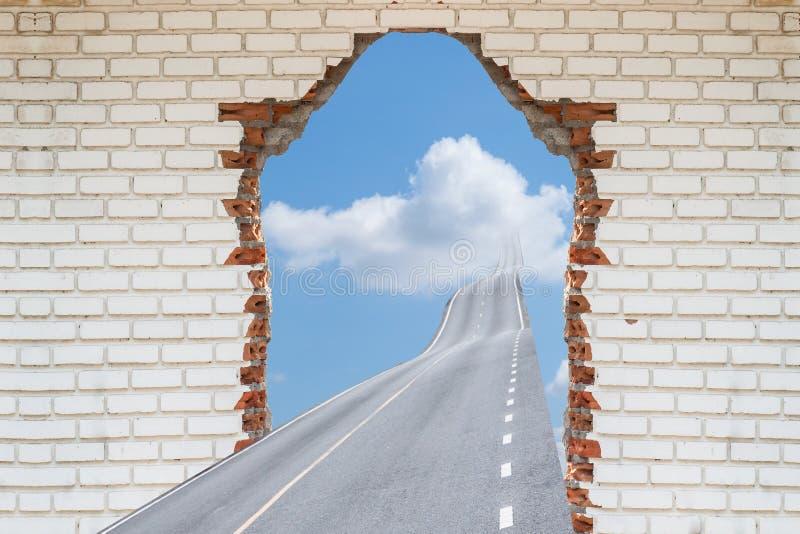 Carretera que pasa a través de una pared de ladrillo quebrada, fotografía de archivo