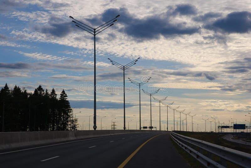 Carretera vacía contra el cielo de la tarde, fila de pilares ligeros, foto de archivo