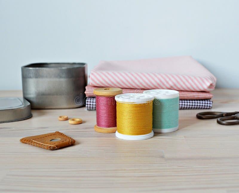 Carretes coloridos del hilo, botones de madera, dedal de cuero, tijeras retras, tarro del metal y telas de algodón imagen de archivo
