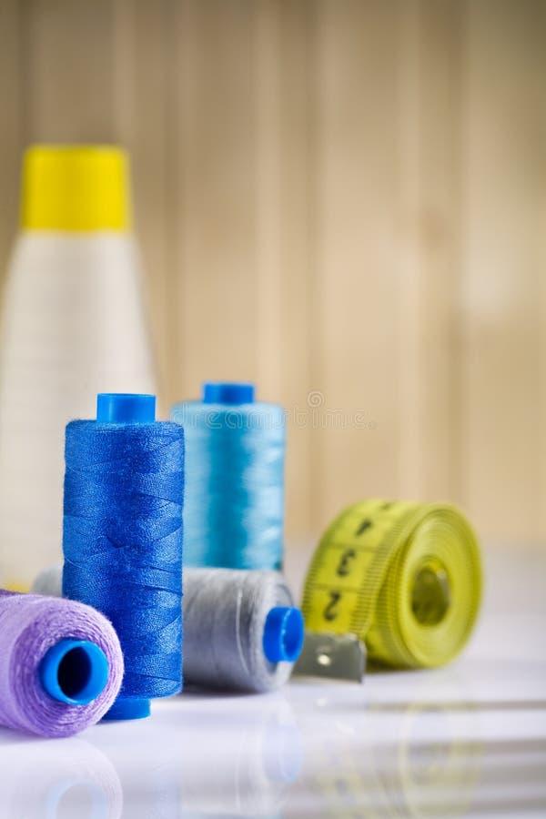 Carretes de costura con las cuerdas de rosca y tapeline imagen de archivo