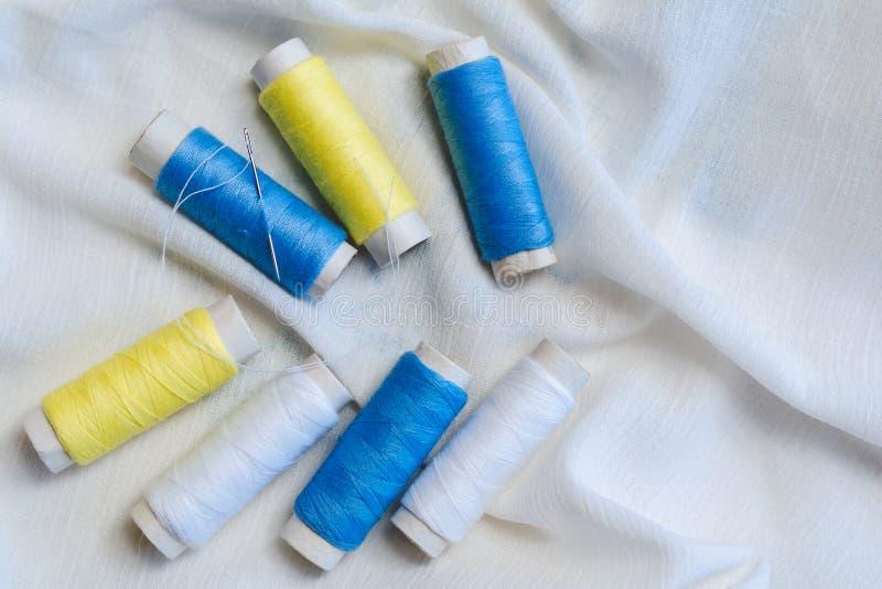 Carretes de hilos y de la aguja de costura azules, amarillos y blancos en el paño de algodón blanco fotografía de archivo libre de regalías