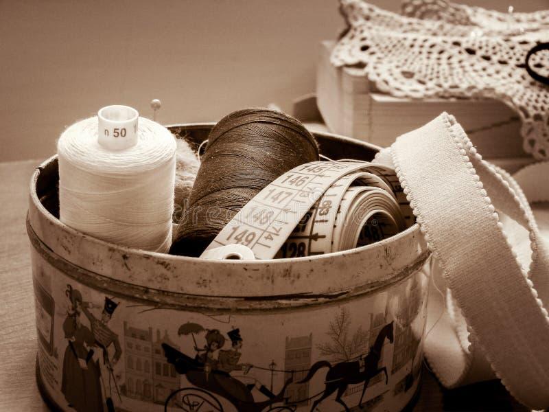 Carretes del hilo a coser en una caja vieja de la lata fotografía de archivo libre de regalías