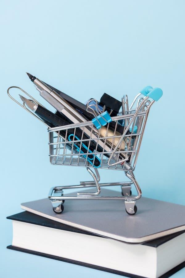Carretilla con diversas fuentes con los libros en fondo azul Educaci?n, de nuevo a la escuela, haciendo compras foto de archivo