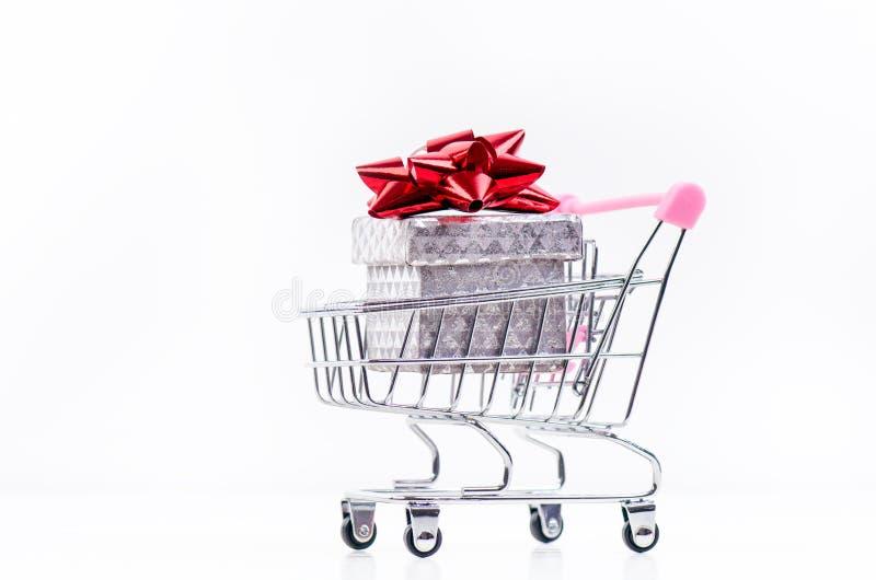 Carretilla de las compras con el regalo de la Navidad Caja de regalo con la cinta roja aislada en un fondo blanco Decoración de l fotos de archivo