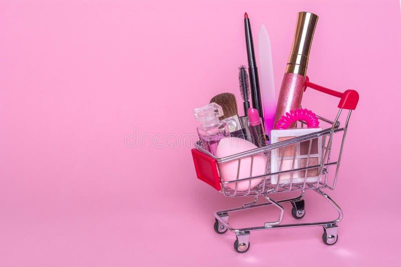 Carretilla de las compras con maquillaje en un fondo rosado Perfume, cepillo, rimel fotografía de archivo libre de regalías