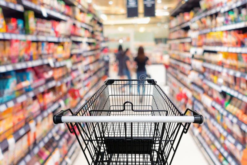 Carretilla de las compras en grandes almacenes con el fondo del estante de las mercancías imagenes de archivo
