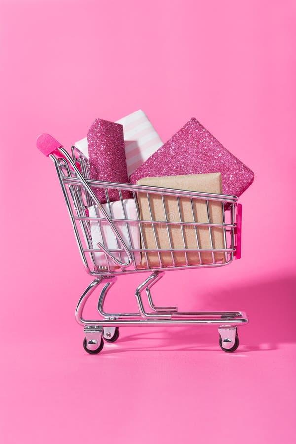 Carretilla de las compras por completo de regalos envueltos en fondo rosado fotografía de archivo