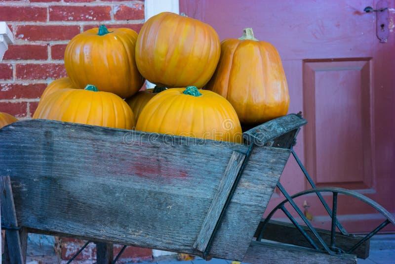Carretilla de OrangePumpkins en el pórtico fotos de archivo libres de regalías
