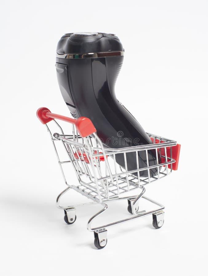 Carretilla del carro de la compra con la máquina de afeitar de la maquinilla de afeitar eléctrica fotos de archivo libres de regalías