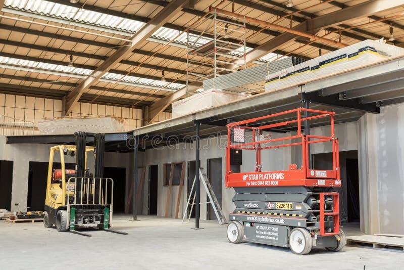 Carretilla elevadora y plataforma de elevación en el co imagen de archivo libre de regalías