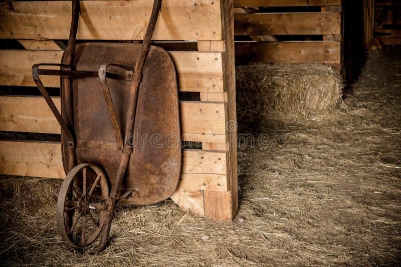 Carretilla envejecida en el granero fotografía de archivo libre de regalías