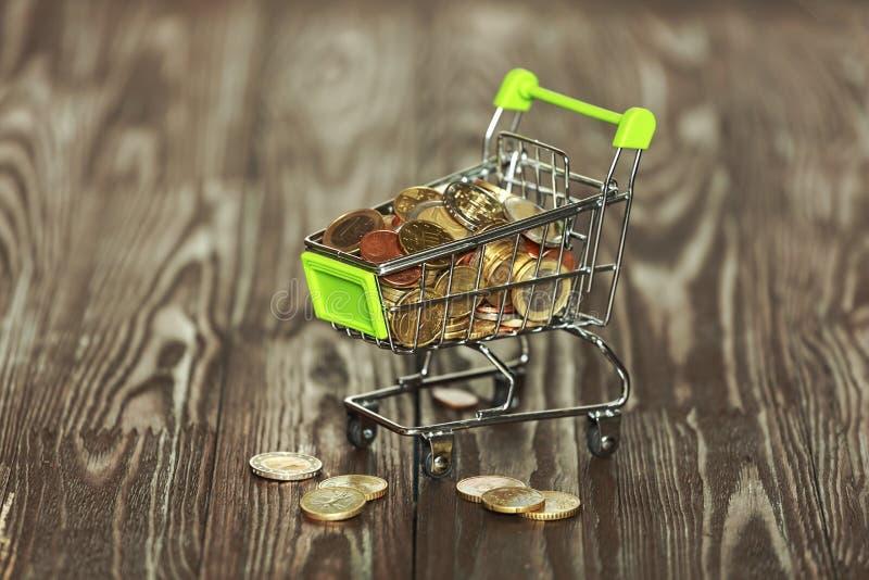 Carretilla, monedas, cesta de compras, compra de mercancías, crecimiento de la renta, inflación, deflación, aumento de precios imagen de archivo