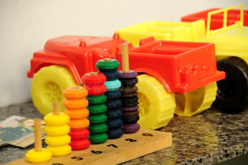 Carretilla plástica y juguetes educativos fotografía de archivo