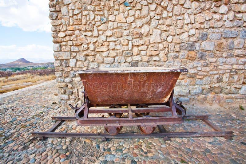 Carretilla rústica vieja de la mina de carbón en los carriles foto de archivo