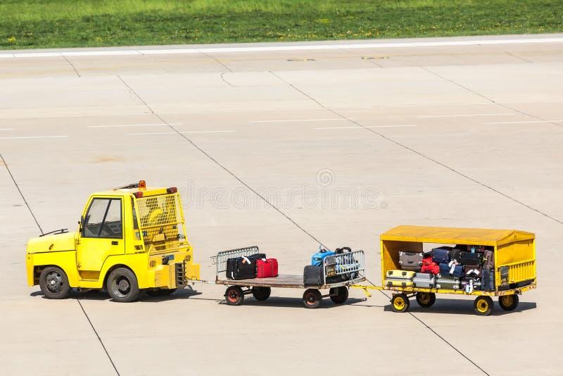 Carretillas amarillas de la carga con equipaje cargado foto de archivo