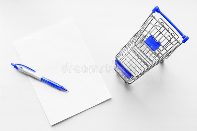 Carretto dalla drogheria e dal foglio bianco di carta con la penna sui precedenti bianchi Idee di affari della lista di acquisto immagine stock
