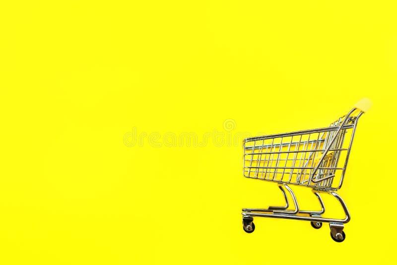 Carretto del giocattolo per i prodotti su un fondo giallo Posto per testo fotografia stock