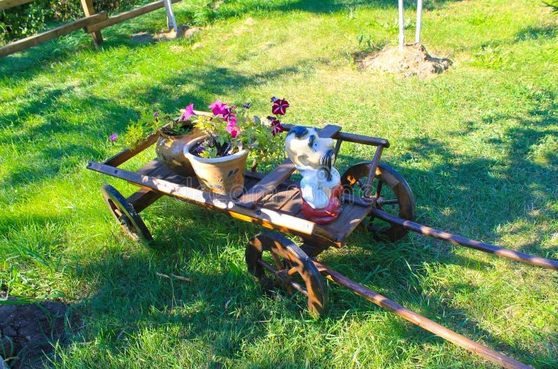 Carretto di legno con i vasi da fiori rustici in giardino for Vasi di legno