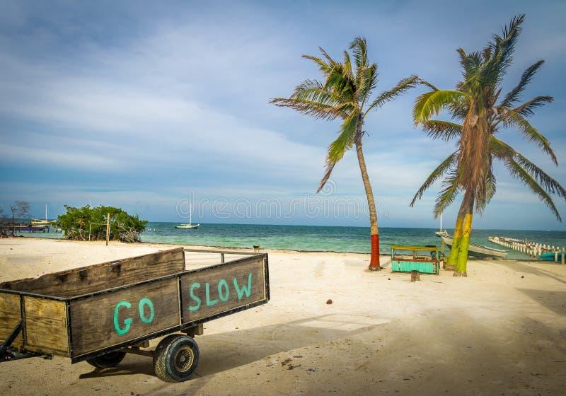 Carretto di legno con il messaggio di rallentamento d'attività al calafato di Caye - Belize immagini stock libere da diritti