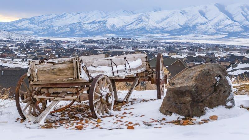 Carretto di legno stagionato di panorama e rocce enormi sopra una collina con neve nell'inverno immagini stock libere da diritti