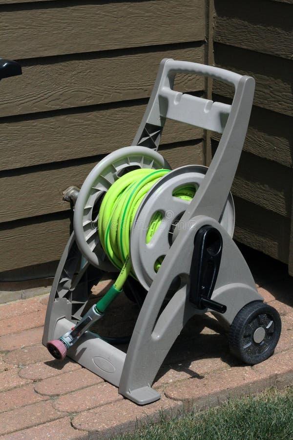 Carretto di plastica dell'avvolgitore per tubo del giardino con le ruote fotografia stock libera da diritti