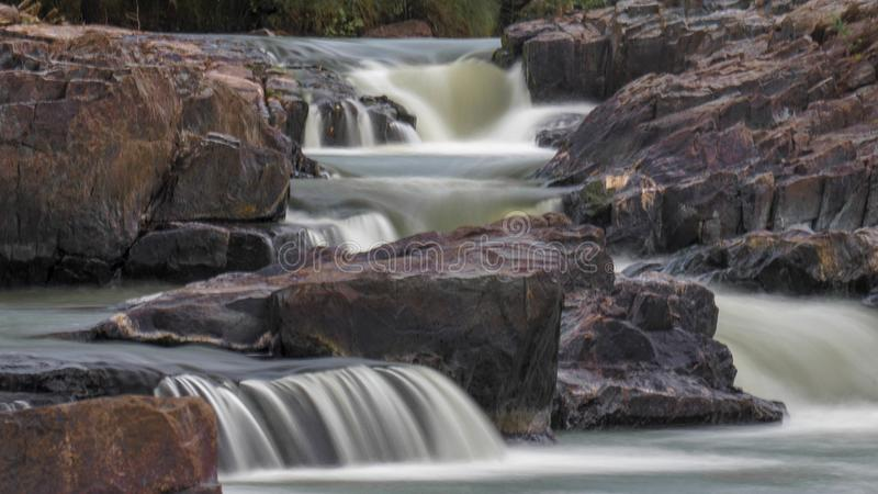 Carrière rocheuse de cascade colorée entourée par des essais verts et des roches peintes photographie stock