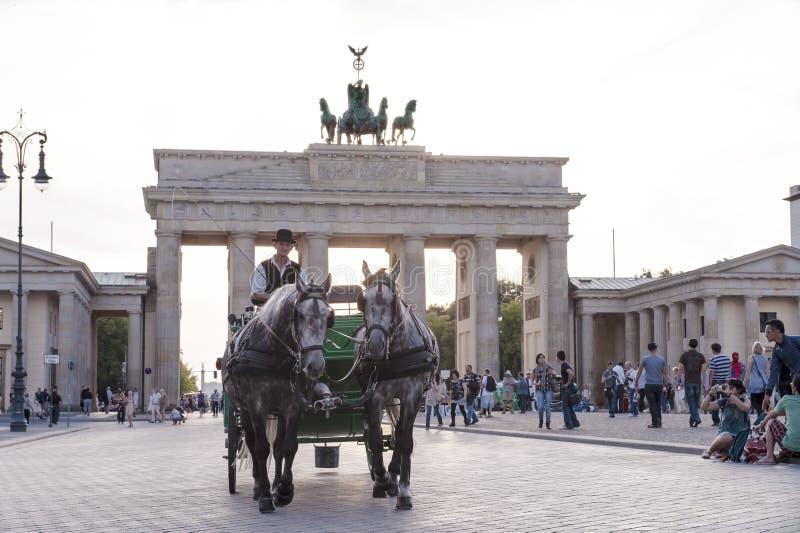 Coachman with horse-drawn carriage at Brandenburg Gate, Berlin, evening at Brandenburger Tor stock image