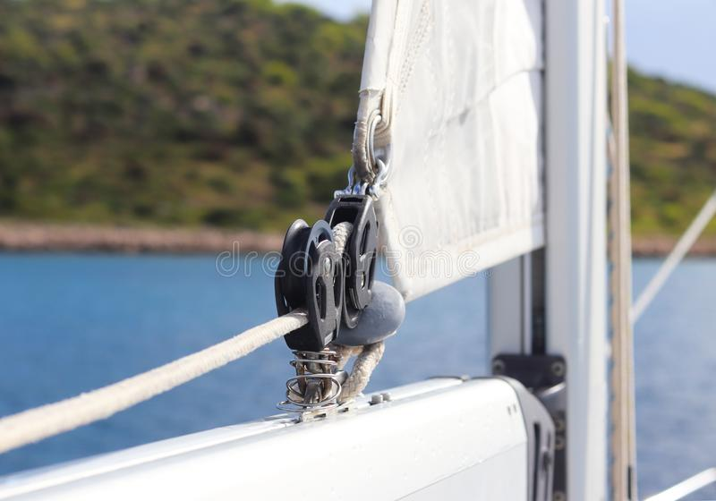 Carriage of the main sail corner at the mainmast on a sailing yacht for sending tracks against the background of the summer sea. O stock photography