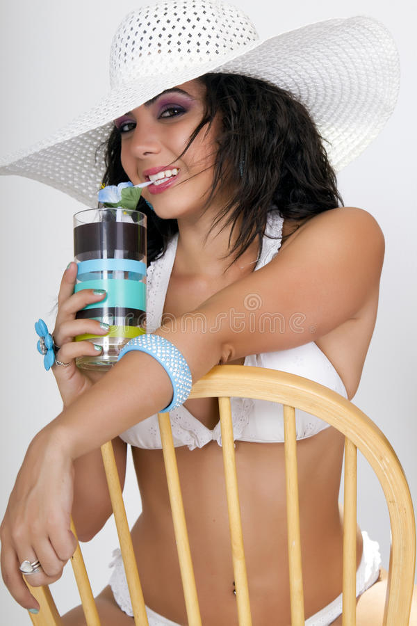 Carribean cocktail at the beach. Lovely young brunette female sporting a white straw hat and white bikini cools off at the beach with an ice cold island cocktail stock photos