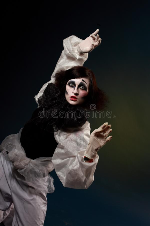 Carried away by the dream. Pierro flying away by his dream. Studio portrait of young girl in Pierrot costume and make-up flying away by the dream royalty free stock photos
