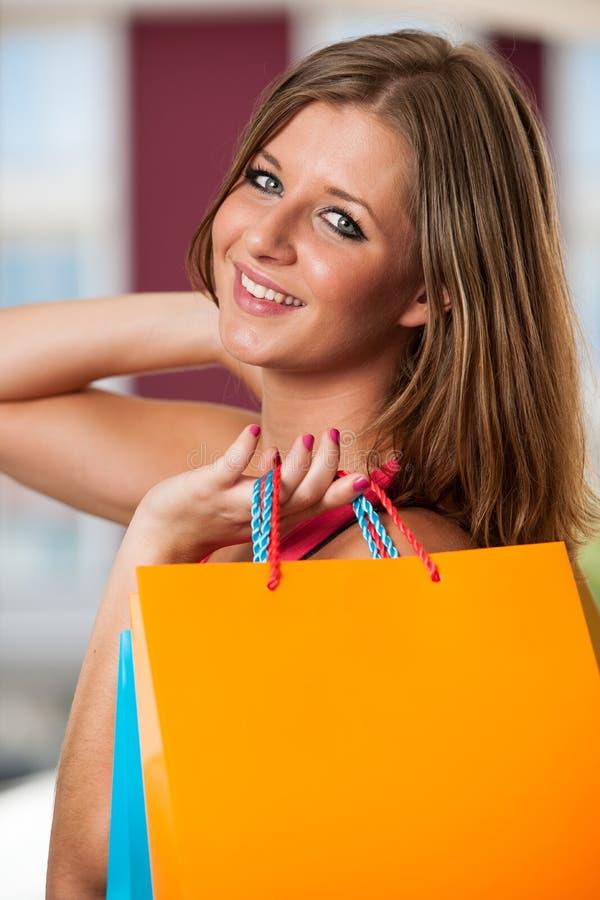 carriing充满活力的购物袋的女孩 免版税库存照片