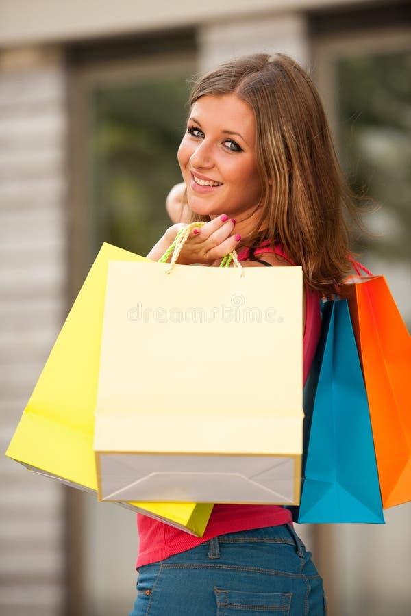 carriing充满活力的购物袋的女孩 免版税图库摄影