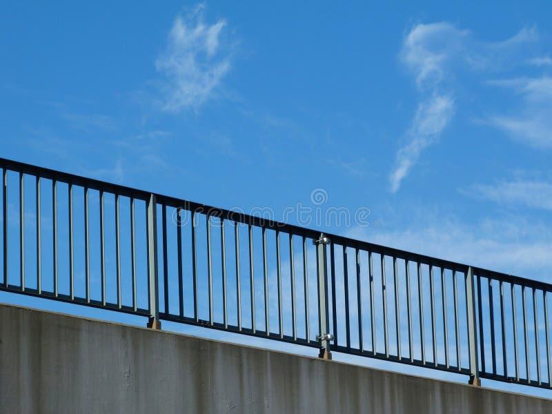Carril de guardia de acero con los piquetes y los postes en la carretera con el cielo azul imagen de archivo
