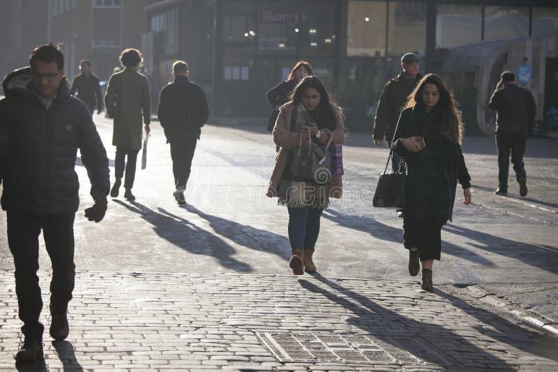Carril del ladrillo de la calle al mediodía en el contraluz Prisa de la gente sobre su negocio Londres del este imagen de archivo