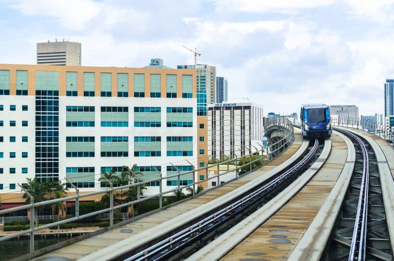 Carriles de Metromover que pasan en la altura entre los edificios y los rascacielos modernos Miami, la Florida meridional, los E. fotografía de archivo libre de regalías