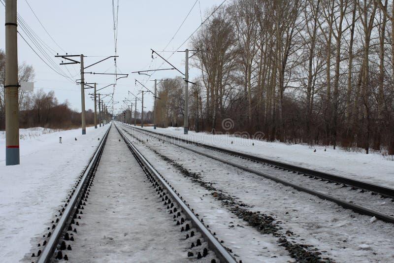 Carriles del ferrocarril que estiran distancia la trayectoria para el tren sitiado por la nieve en el invierno imagenes de archivo