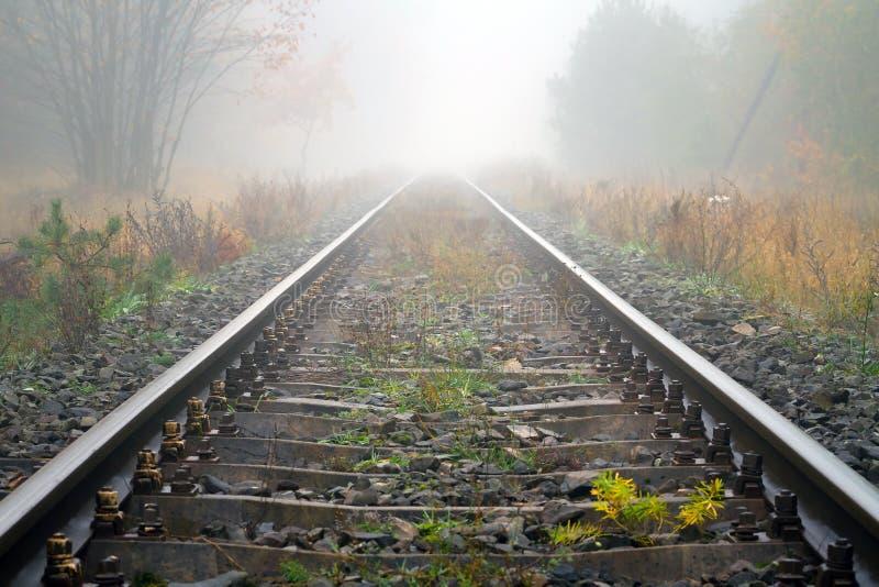 Carriles Del Tren En Tiempo Brumoso Fotos de archivo